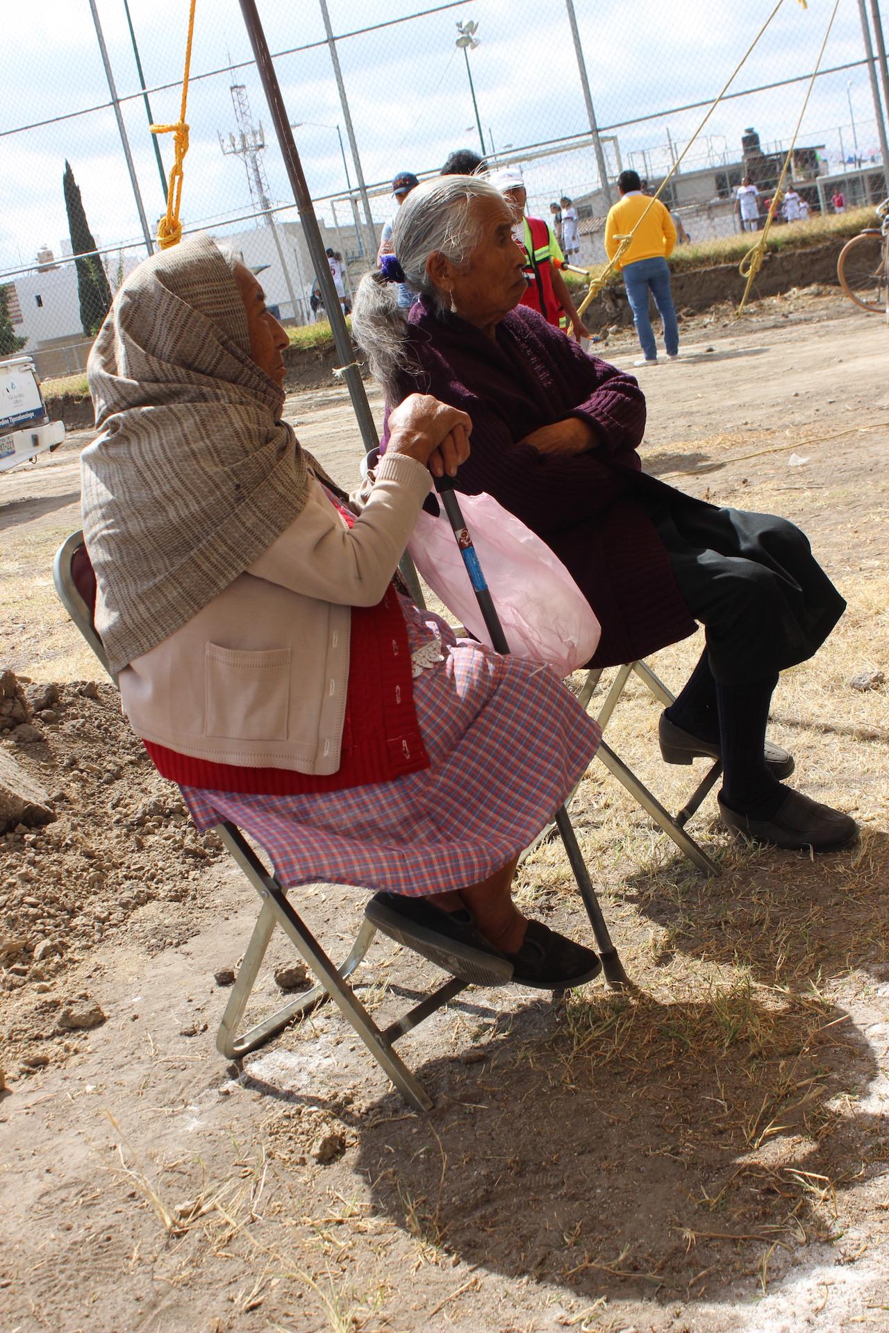 Abuelitas esperando el inicio para la colocación de la primera piedra.